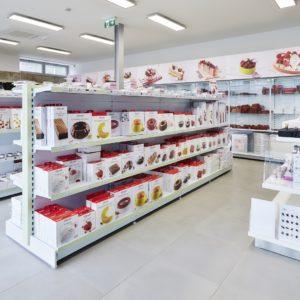 pohled do prodejny na regály v bílé barvě, Almeco - Praha