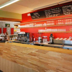 Červená barva stěny v zápultí vhodně doplňuje barvu dřeva na pultě