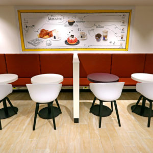 Čalouněná lavice, stolky z naší výroby doplněné grafikou Panos.