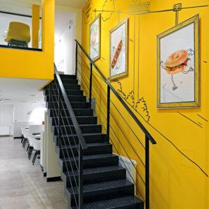 Kovové schodiště v černé barvě vytváří pěkný kontrast se žlutým nátěrem zdi.
